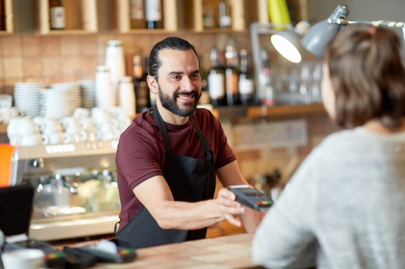 man or waiter with card reader and customer at bar