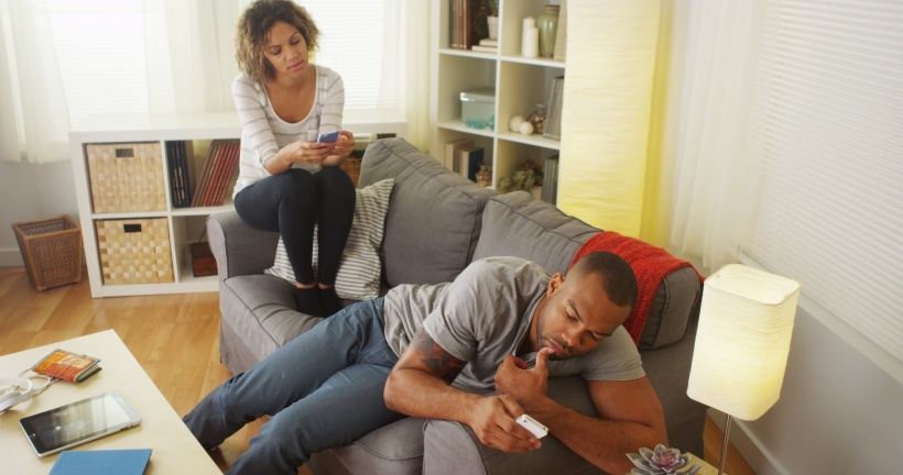 Black couple distracted by smartphones